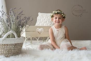 Kinderfoto - Mädchen mit Blütenkranz im Haar auf flauschigem Fell in Fotoatelier