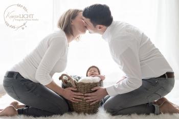 Baby-im-Korb-Eltern-halten-das-Neugeborene-mit-Muetzchen