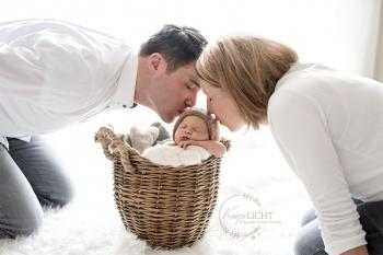 Familienfoto-Eltern-küssen-Baby-mit-Muetzchen-im-Korb
