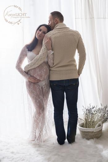 Schwangere-im-Spitzenkleid-kuschelt-sich-an-ihren-Mann-Backlightning