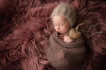 Baby mit Mützchen hält ein Herz fest in der Hand