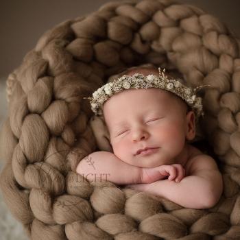 Baby mit Blumenkranz liegt auf dem Bauch