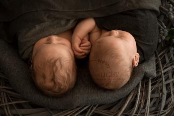Fotos von Neugeborenen Zwillingen die Händchen halten