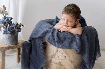 Babyfotos von schlafendem Newborn mit vielen Haaren in der Kinnpose