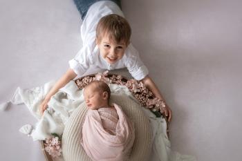 Bruder und Schwester beim Fotoshooting des neugeborenen Babys