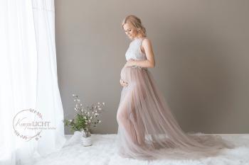 Babybauchshooting im Fotoatelier mit Blumen und Schwangerschaftskleid
