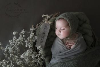 schlafendes Baby mit Mütze in zartem grün